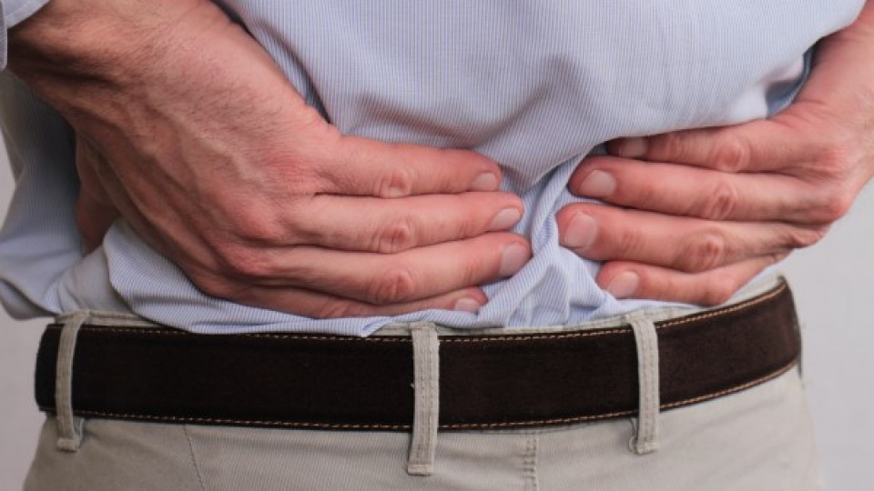 Close up of business man holding his lower back.  Man rubbing his painful back